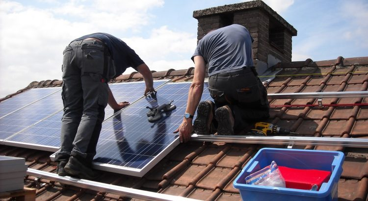 2 men installing solar panels on roof